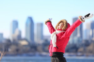 City winter woman happy standing excited and elated with arms ra