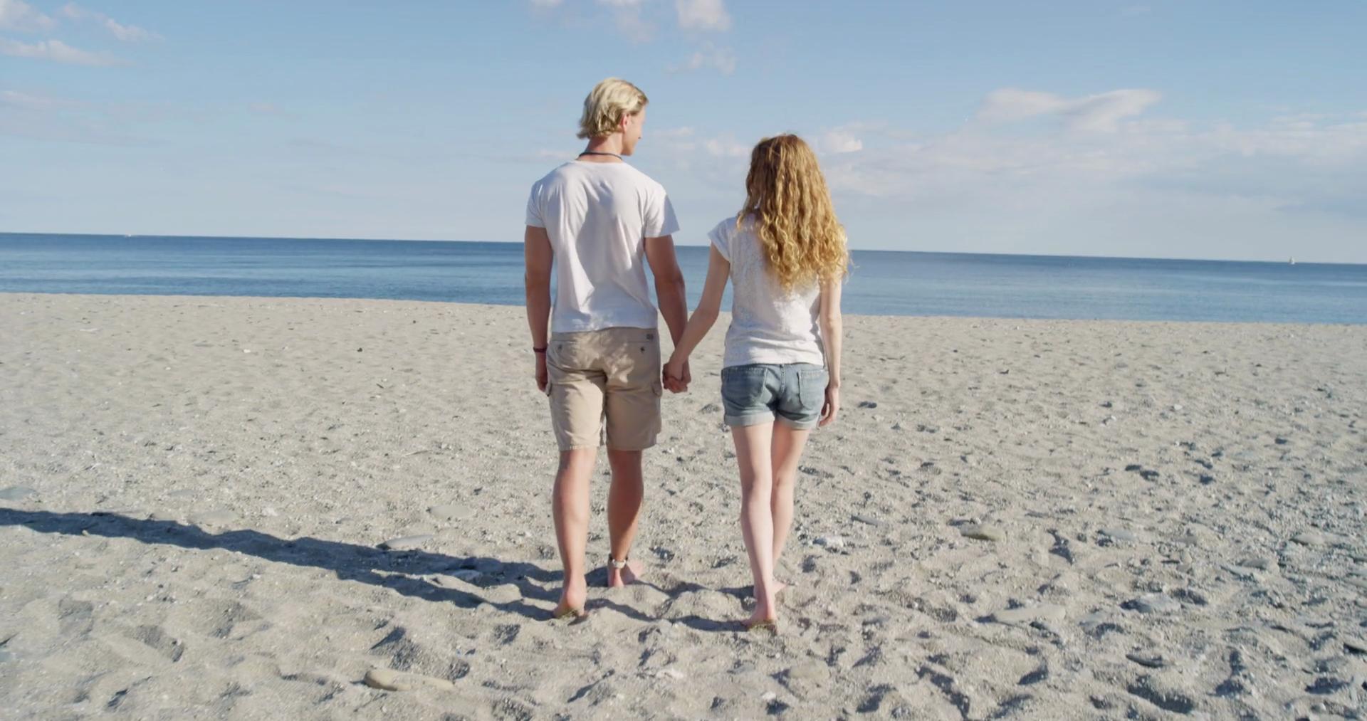 young couple walking toward ocean